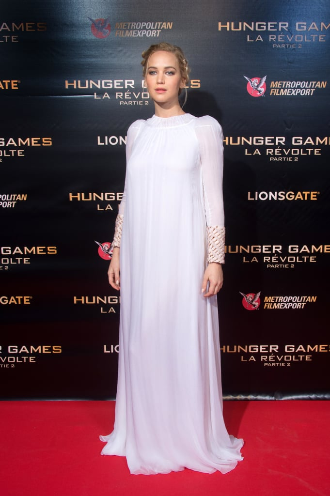 For The Hunger Games: Mockingjay Part 2 red carpet in Paris, she wore a Dior Couture white dress was made of chiffon and featured fur sleeves. Jen's outfit was finished with jewels by Shay Jewellery and Dana Rebecca, and she wore Sophia Webster heels.