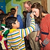 Will and Kate were greeted with a tilak by children at a charity center during their trip to India in April 2016.
