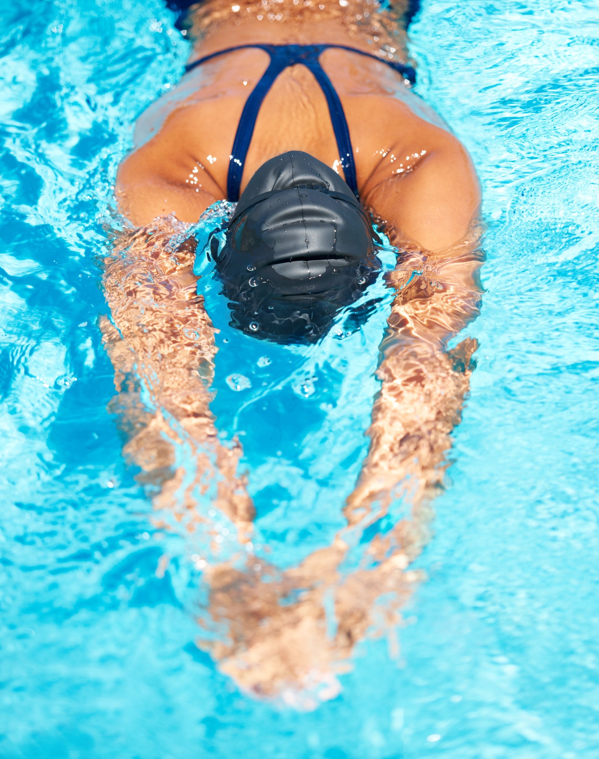 Shot of a young female swimmer gliding through the water