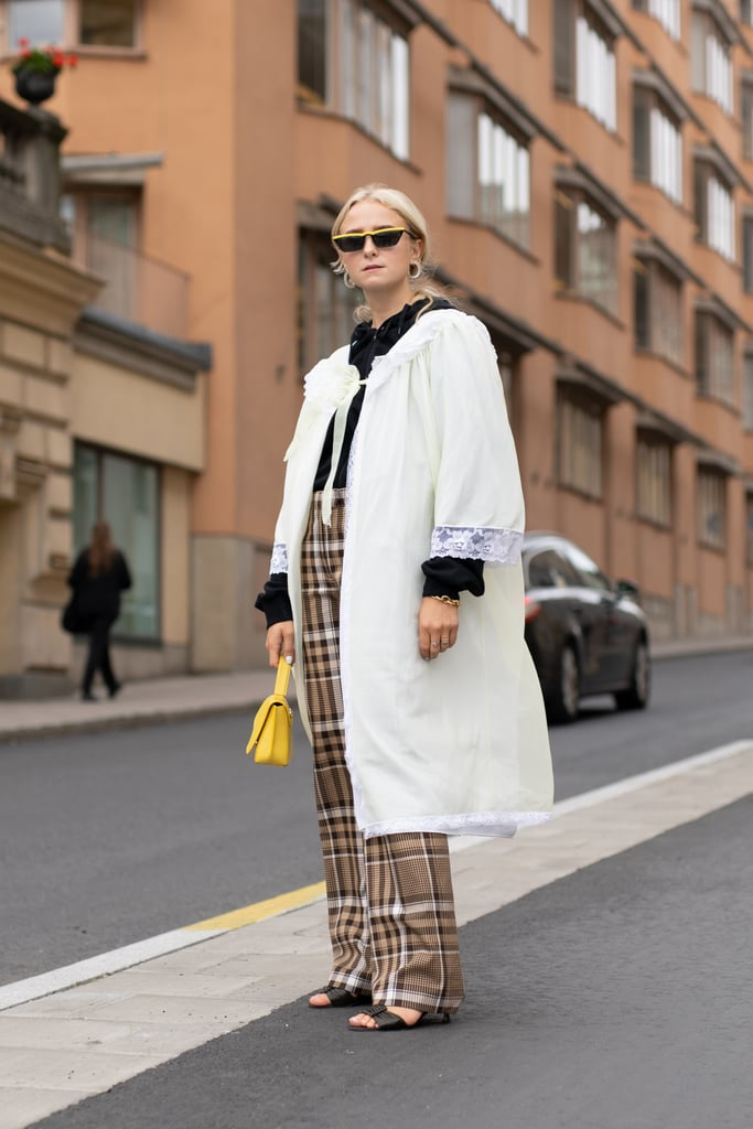 Pare down bold plaid pants with a clean white overcoat.