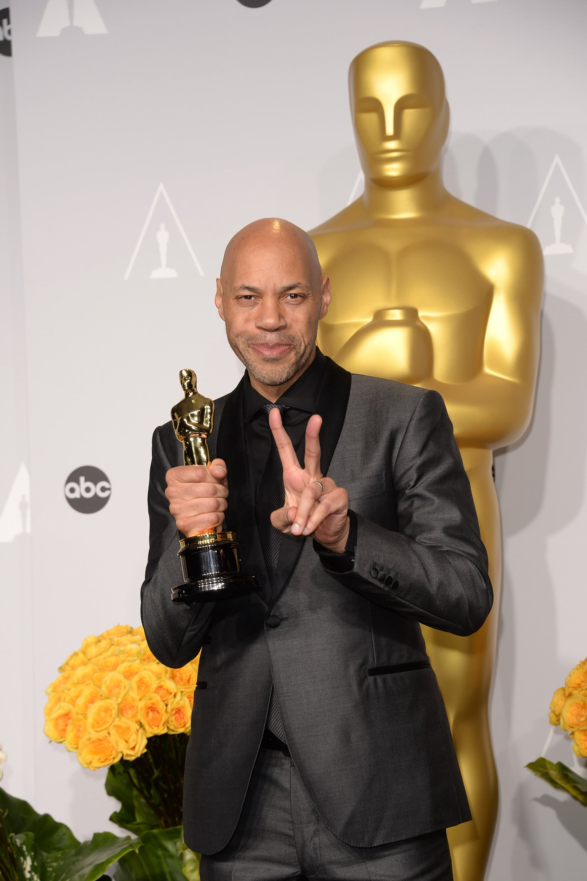 12 Years a Slave writer John Ridley flashed a peace sign with his Oscar for best adapted screenplay.