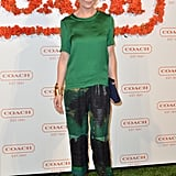 Ellen Pompeo was the picture of Spring in bloom, just by way of her silky printed pants and complementary green silk top. She accented the look with a Coach Legacy perforated clutch.