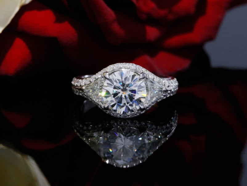 Three stones fool your eyes into seeing one giant diamond in this brilliant halo engagement ring ($2,690) in 18k white gold.
