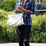 Styling a plaid shirt with distressed denim and a Balenciaga bag in 2008.