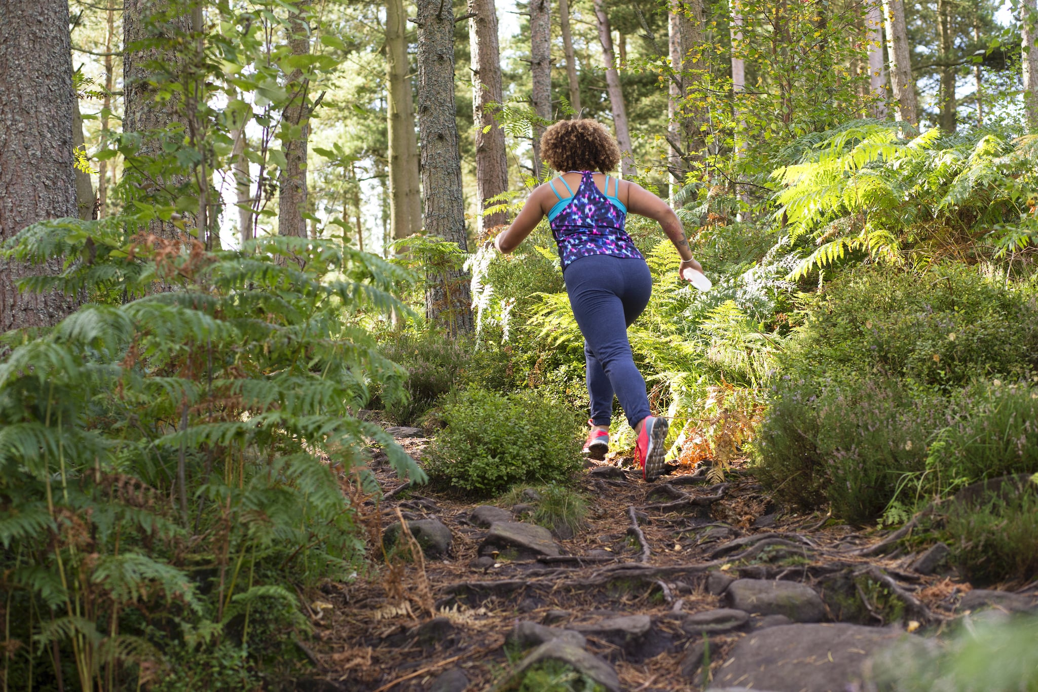 Rear view shot of a woman running through a forest across extreme terrain. She is wearing sportswear and is carrying a waterbottle.