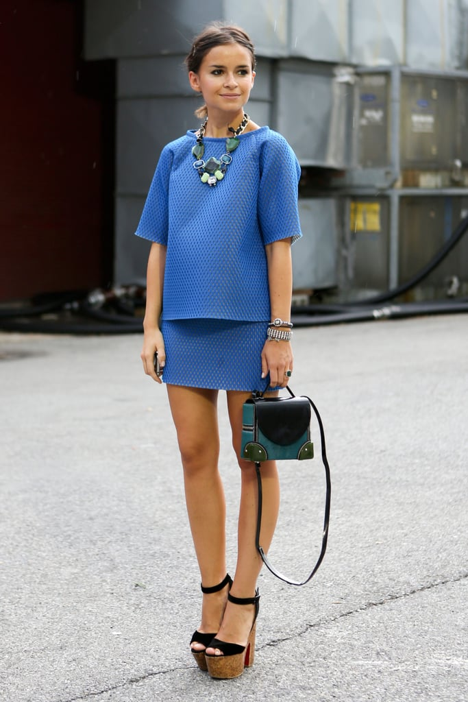 Miroslava Duma charms in a blue skirt-and-top set — with her signature statement jewels and platforms.