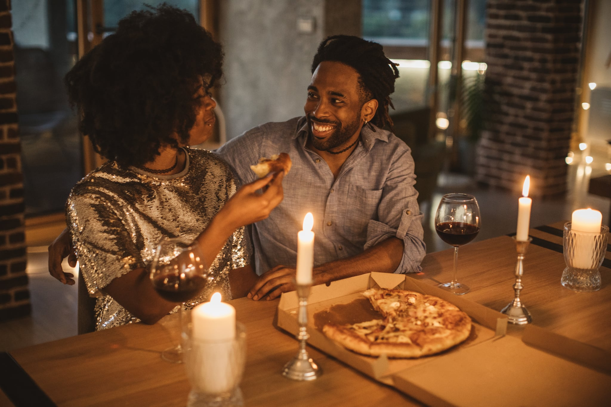 Young couple having romantic dinner at home. Eating pizza and drinking wine. Well dressed.