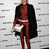 Karolina Kurkova looked menswear chic in a navy-and-crimson-striped suit and sleek white tote, all by Michael Kors, at the designer's show.