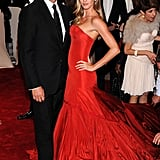 Gisele Bundchen opted for a red floor-sweeping Alexander McQueen strapless gown with a streamline silhouette on top and pleats down below.