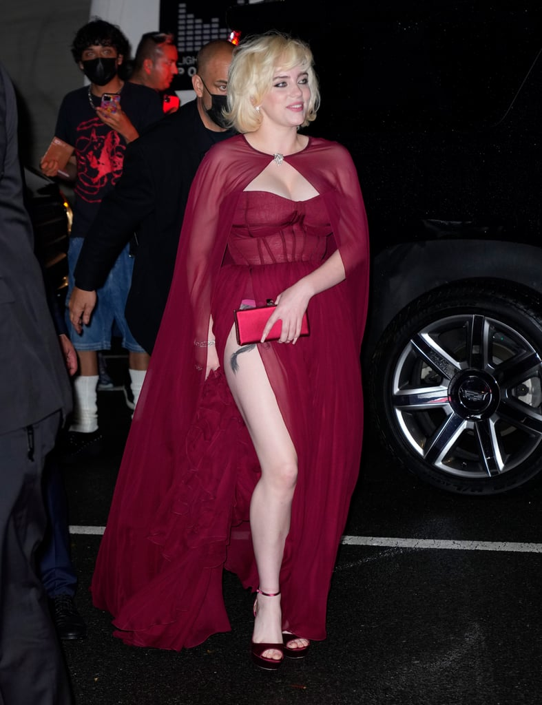 """Celebrities left it all on the Met Gala steps on Sunday: romantic gowns, elaborate but inspiring ensembles, and even golden robot armor. But inside the venue, a few attendees took the opportunity to wear a second outfit just as extravagant as the first. For Met Gala cochair Billie Eilish, who played on this year's """"American Fashion"""" theme with a Marilyn Monroe-inspired ballgown, it only made sense to stick with her Old Hollywood inspiration and change into a wine-colored Oscar de la Renta cape dress.  Like something straight off of a Hollywood red carpet from the 1950s, Billie's dress featured a corset-style bodice, a ruffled hem, and a flowing chiffon skirt with a thigh-high slit that gave us another peek at the tattoo on her right leg. The complementary sheer cape was fastened at the base of her throat with a silver brooch that beautifully matched her jewelry for the evening, and Billie rounded out the look with a red clutch and matching heels. See her second Met Gala outfit from all angles here.       Related:                                                                                                           The Meaning Behind Amanda Gorman's Royal Blue Met Gala Look Is as Beautiful as Her Dress"""