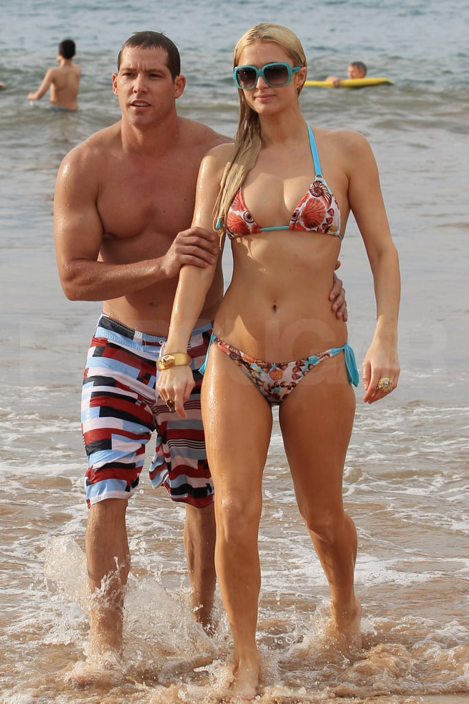 Paris Hilton's man Cy Watts couldn't keep his hands off her as they had fun on the beach in Hawaii yesterday. She and Cy kissed on beach loungers and walked together on the beach, before splashing around in the sea with Paris' sister Nicky. Paris was in Madrid at the start of the week, and looked relaxed following a scary start to the holiday as a knife was found on the plane she was travelling on. Paris matched her halterneck straps to her sunglasses for her time on the beach, after wearing a cutout black swimsuit earlier in the week, while Nicky wore a cute strapless two-piece in blue.