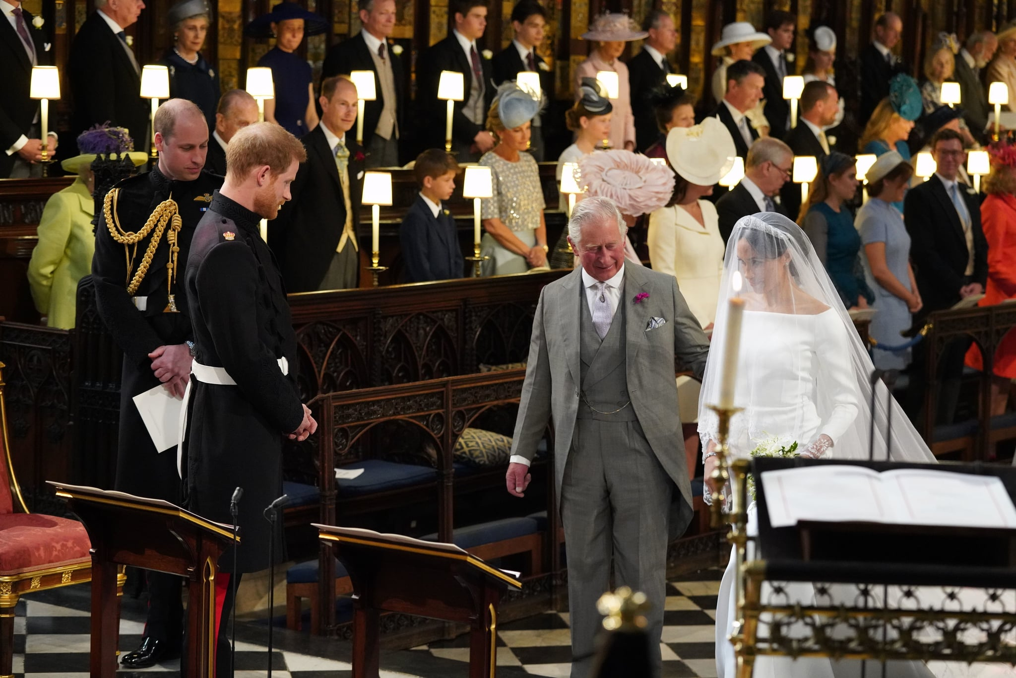 TOPSHOT - Britain's Prince Harry, Duke of Sussex (2nd L), looks at his bride, Meghan Markle, as she arrives accompanied by the Britain's Prince Charles, Prince of Wales in St George's Chapel during the wedding ceremony of Britain's Prince Harry, Duke of Sussex and US actress Meghan Markle in St George's Chapel, Windsor Castle, in Windsor, on May 19, 2018. (Photo by Jonathan Brady / POOL / AFP)        (Photo credit should read JONATHAN BRADY/AFP/Getty Images)