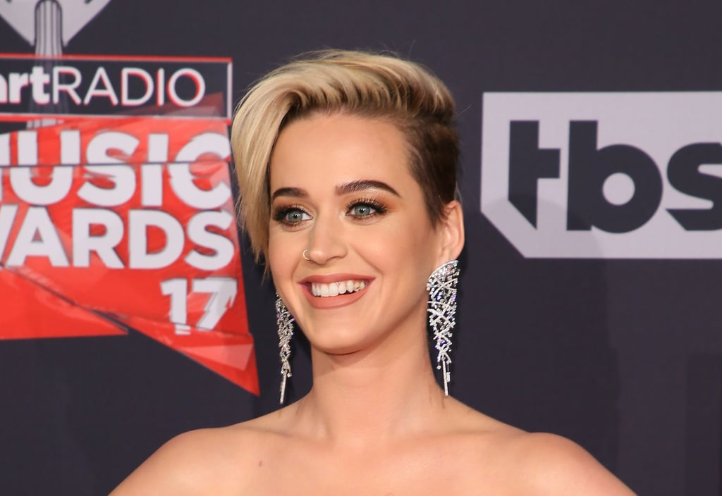 An edgy new hairstyle isn't the only thing Katy Perry debuted on the iHeartRadio Music Awards red carpet. The singer wore a white and gold jumpsuit and added some dazzling tooth jewelry to top it off. Yes, you read that correctly — tooth jewelry. Not to be confused with the tooth tattoo trend, Katy's molar jewelry looks like a tiny gold Nike swoosh, and it shone bright every time she flashed a smile for the cameras on the red carpet. Situated on the left side of her mouth, this tooth jewelry is like a more personalized, chic version of grills, and we're beyond intrigued by the new trend. It looks like Katy has had this interesting molar accessory for quite some time, as she shows it in some of her past social media posts. But her latest red carpet saunter — and a funny Instagram post in which she gives her followers a close-up look at her quinoa-ridden smile — has put her quirky tooth accessory in the spotlight. Keep reading to see Katy's gold-adorned smile.