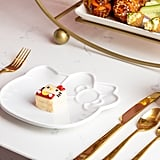 The table is set with Hello Kitty plates and gold flatware.