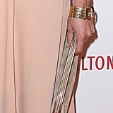 Cat Deeley finished her look with an understated neutral clutch and a gold buckled cuff.