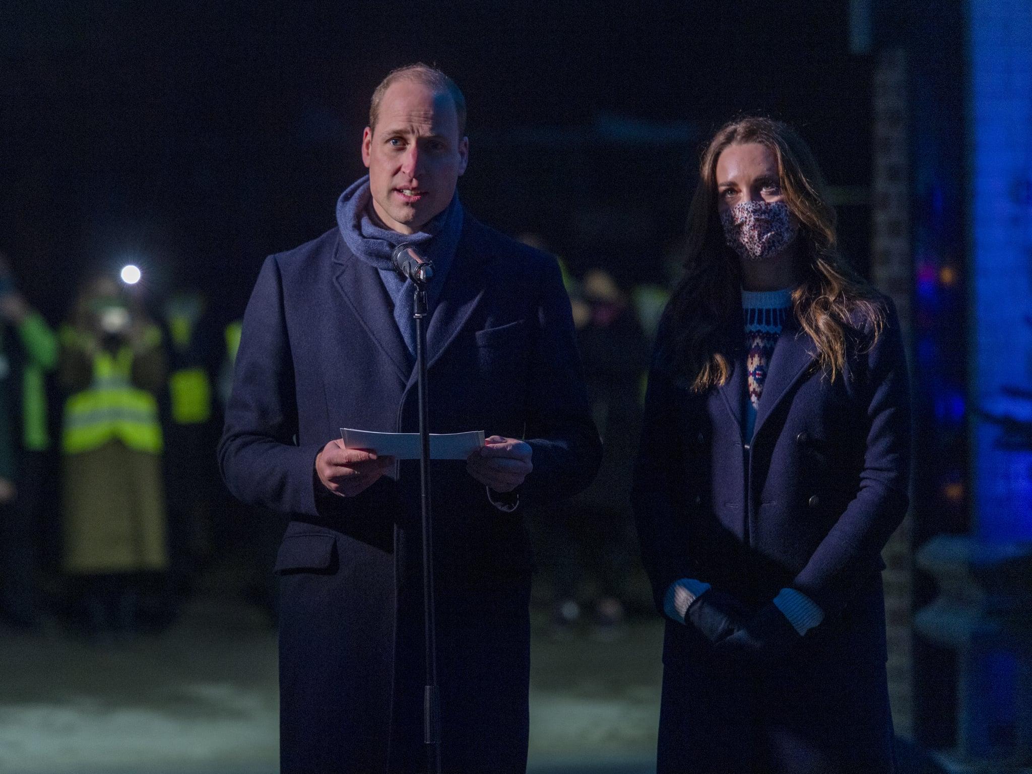 William e Kate estão em pé. William segura um papel e olha para frente. Eles estão com as mesmas roupas do desembarque.