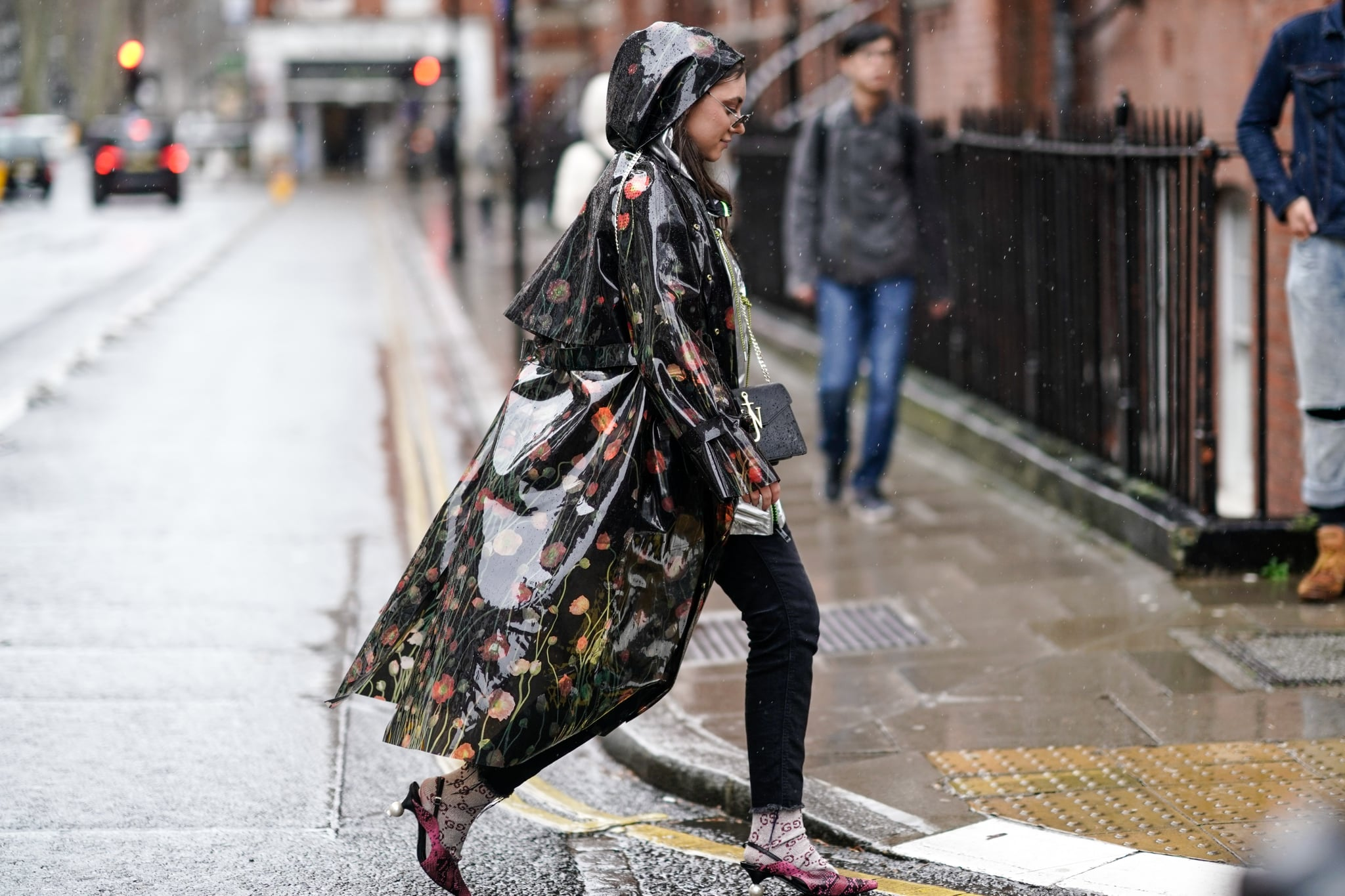 LONDON, ENGLAND - FEBRUARY 18: A guest wears sunglasses, a glossy floral printed vinyl raincoat, a black JW Anderson bag, black ripped hem jeans, Gucci socks, pink python pattern pumps with pearl heels, during London Fashion Week February 2019 on February 18, 2019 in London, England. (Photo by Edward Berthelot/Getty Images)