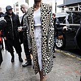 Outside the Christian Siriano show during NYFW, Zendaya layered feathers, knits, and one eye-catching gold-and-black coat.
