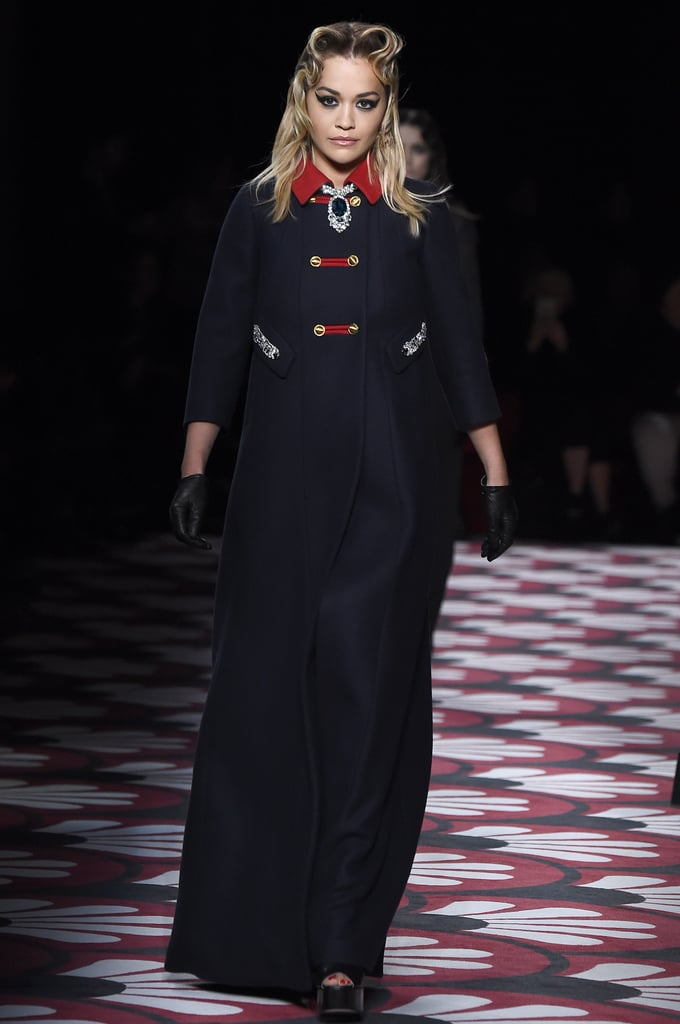 "Rita Ora just added another skill to her CV: runway model. She walked the Miu Miu Autumn/Winter 2020 runway during Paris Fashion Week on Tuesday — and she looked like a total pro.  The singer-songwriter wore a floor-length, navy jacket with red detailing on the collar and chunky, open-toed platform heels — accessorised with black gloves and a statement sapphire necklace. Rita's hair and makeup was equally eye-catching. She wore striking winged eyeliner — designed by makeup artist Pat McGrath, who used her brand's liquid liner to create the look — which encircled both her top and bottom lids and stretched right out toward her temples. Her hairstyle — which all the models wore for the show — was styled in a centre part with two overexaggerated finger waves that were gelled in place. ""The hair at Miu Miu this season was based on the '40s, but with a twist on the '70s, too,"" hairstylist and Redken Global Creative Director Guido Palau said of the look via a press release sent after the show.  Rita was in good company on the runway, too. Known for recruiting celebrities to walk to show, Miu Miu also invited 16-year-old actor Storm Reid to walk, in addition to the season's catwalk superstars Gigi and Bella Hadid, Kaia Gerber, and Pixie Geldof."