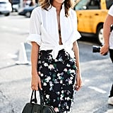 Kelly Framel exudes femininity with a tied white blouse and a floral knee-length skirt.