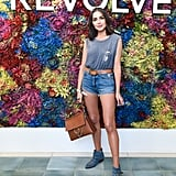 Olivia Culpo wearing jean shorts, a muscle tee, denim boots, and a Chloé bag at the Revolve festival.