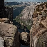 Stand on a Boulder Wedged Between Mountains in Norway