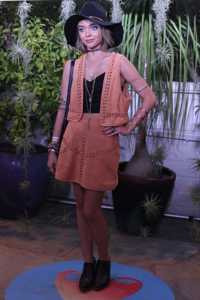 At the H&M x Coachella party, Sarah Hyland's perfect suede set was accented with layers of jewelry, flash tattoos, and black pieces like a crop top, ankle booties, and a fedora.