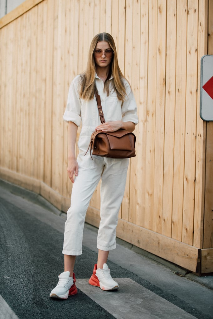 There's something downright chic about a pair of sleek sneakers and an understated jumpsuit.
