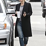 Drew Barrymore wore jeans and a t-shirt under a long black jacket.