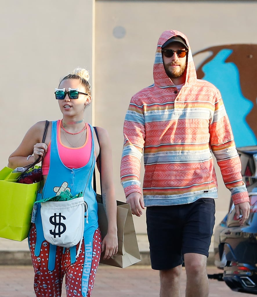 """Miley Cyrus and Liam Hemsworth shared a couple of goofy moments while leaving a store in Malibu, CA, on Sunday. The couple surveyed their new merchandise as they made their way out of the store with a group of friends and pretended to fly like airplanes while heading to their car. Miley and Liam's outing comes on the heels of reports that they have postponed their upcoming wedding and canceled a honeymoon trip to Bora Bora. A source close to Miley told Us Weekly, """"They had the entire trip planned, but Miley just decided she didn't want to go there anymore"""" and that """"they have yet to pick a new locale."""" The source also added that the couple hasn't been consistent about their wedding date, either. Miley is reportedly """"very erratic with her decision-making"""" and changed her mind about tying the knot in the Summer, now opting for a Fall wedding. For what it's worth, Miley wasn't wearing her engagement ring during their afternoon of errands."""