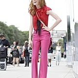 Red and pink is the color combo to wear right now. This street-snapped look shows the trend perfectly, from the perfectly flared pants to the femme ruffled top. Click on to shop the same chic outfit.