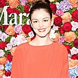 Burnt orange lipstick and a topknot were a bold combination for Nora Zehetner at the Max Mara celebration, and the colors blended perfectly with the summery floral background.