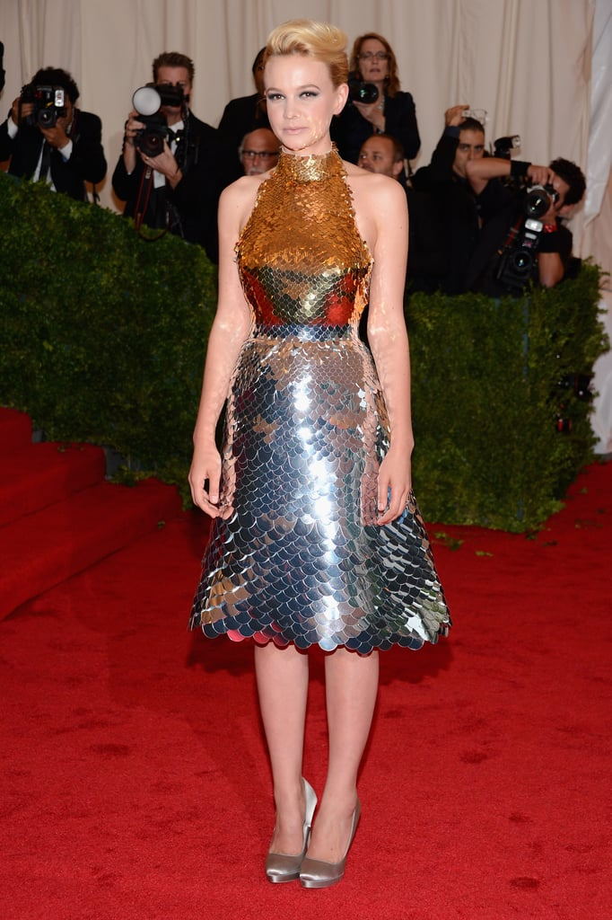 "Carey Mulligan wore a show-stopping gold sequinned Prada dress for the Met Gala in NYC today. The actress, who recently married Mumford & Sons lead singer Marcus Mumford in an intimate ceremony in Somerset, England, is co-chairing the event today with US Vogue editor-in-chief Anna Wintour. Carey's dress honours Italian designer Miuccia Prada, who is one of the subjects of this year's ""Schiaparelli and Prada: Impossible Conversations"" theme. This is Carey's first red carpet as a newlywed and the first time we get to see her wedding ring. Weigh in one Carey's look by voting on Fab and Bella's polls."