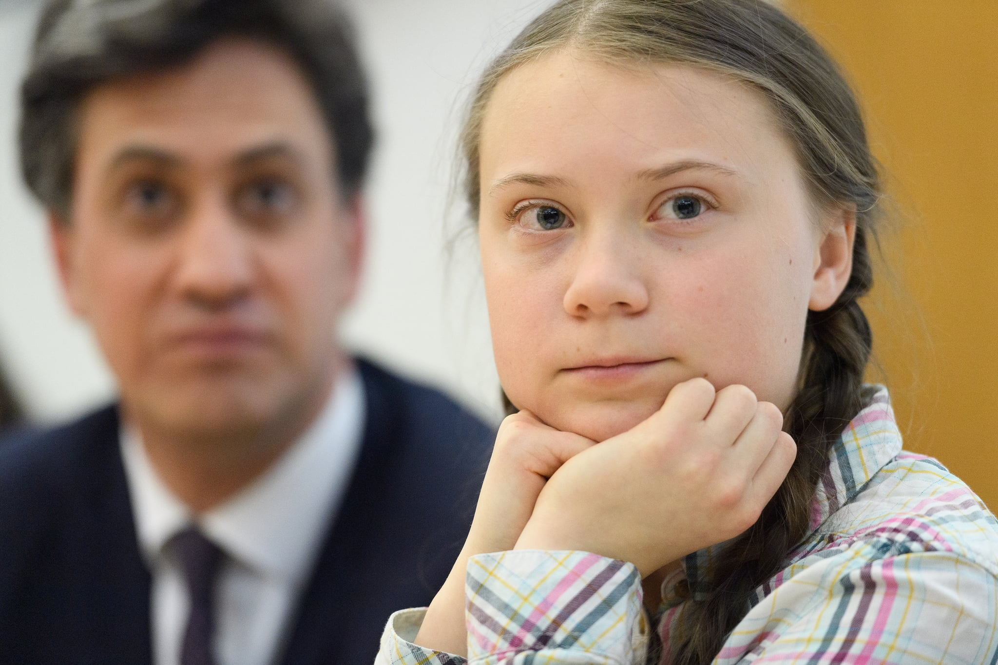 LONDON, ENGLAND - APRIL 23: Former Climate Change Minister Ed Miliband (L) looks on as Swedish environmental campaigner Greta Thunberg addresses politicians, media and guests with the Houses of Parliament on April 23, 2019 in London, England. Her visit coincides with the ongoing