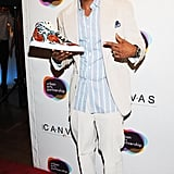 Nick Cannon held a sneaker at the Project Canvas Exhibition & Art Gala in NYC.