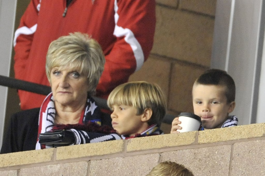 Cruz Beckham stayed warm with a hot beverage, sitting with brother Romeo and grandmother Sandra.