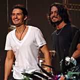 Pirates of the Caribbean costars Orlando Bloom and Johnny Depp accepted a colorful surfboard award in 2006.