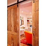 The master suite includes a lounge area separated with custom sliding reclaimed lumber doors.