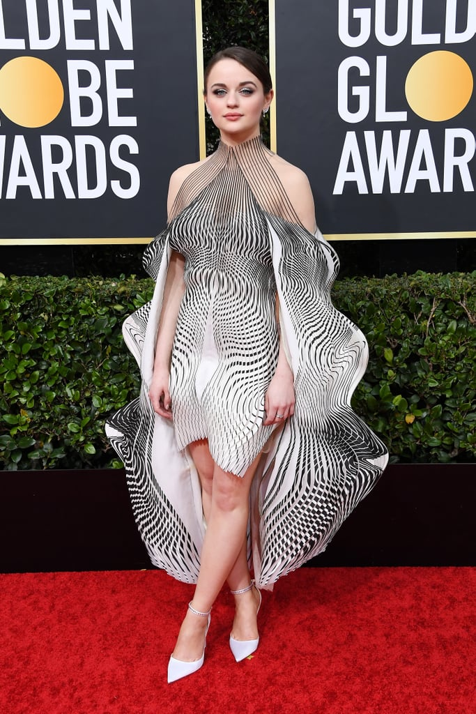 The stars are out and their looks are shining at the 77th annual Golden Globes in Beverly Hills on Sunday, and Joey King's hypnotic Iris van Herpen gown is no exception. The architectural design of the black and white dress — which was made as part of Iris's 2019 Hypnosis collection — made Joey look like a living sculpture on the red carpet and created a mesmerising optical illusion from all angles — look at her dress from behind!  Joey paired the linear design with white eye shadow, chandelier earrings, and strappy white heels with bejeweled detailing. Flowing, futuristic, and absolutely angelic, the hypnotizing gown transformed the The Act star into a walking piece of art, and I already know I'm going to be thinking about this look all week. Keep scrolling to take a closer look at Joey's stunning dress from all angles.      Related:                                                                                                           Every Stunning Red Carpet Look From the 2020 Golden Globes