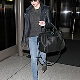 Emilia Clarke kept her style palette dark at LAX. She paired a gray sweater with a leather biker jacket, skinny denim, and cap-toe booties.