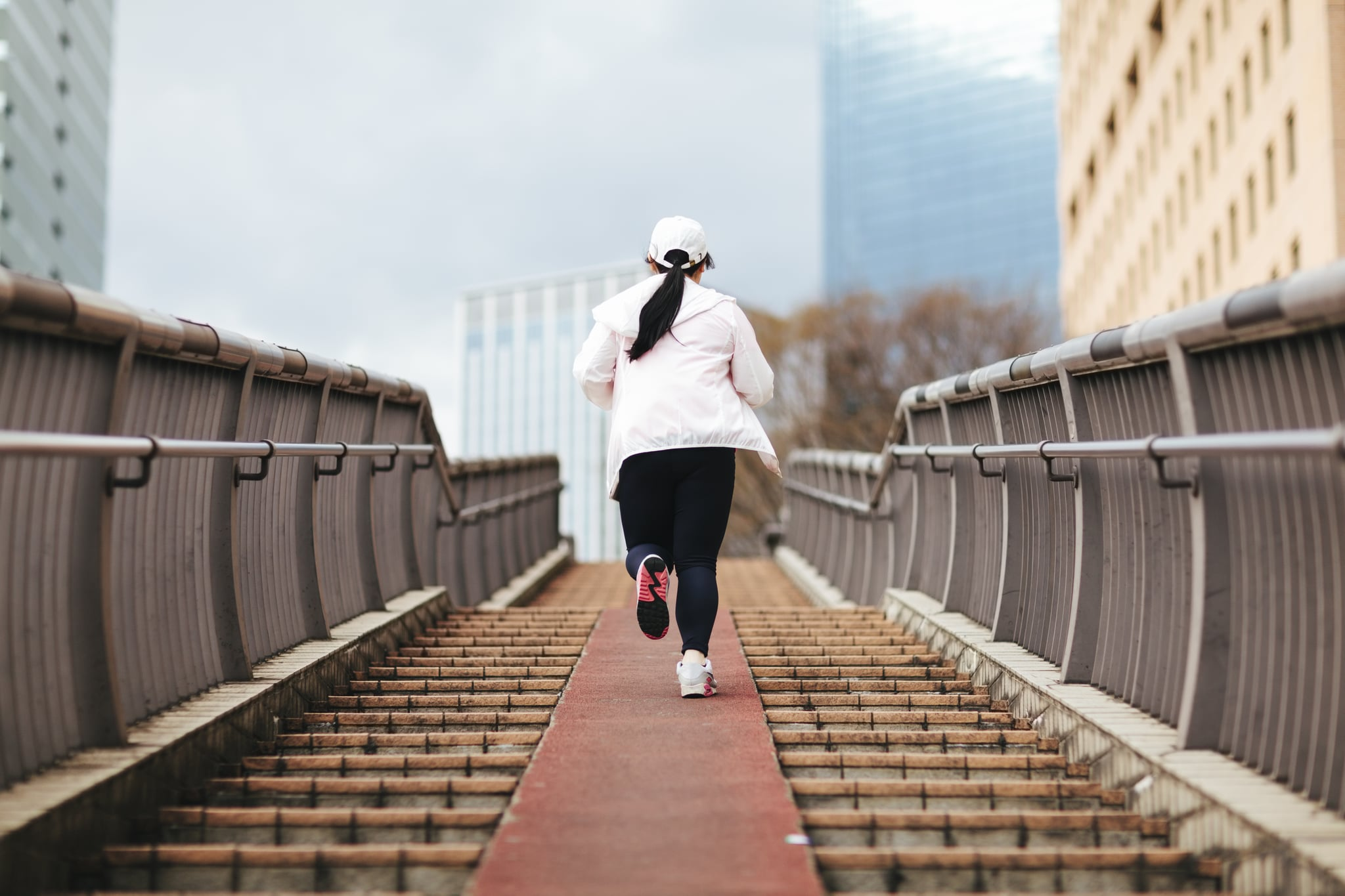 An overweight young Japanese woman is training in the city.