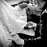 The hem of a Zuhair Murad dress is checked before it hits the catwalk.