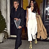 Amal ditched the dress for date night with George, selecting a chic, functional white Stella McCartney jumpsuit instead. She completed her look with bright eye-catching heels, then played up their yellow shade with golden accessories: a metallic clutch and geometric drop earrings.