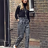 Cressida's loose tartan pants are just right — they're a neutral and not too distracting to take away from her accessories. With the addition of a silver wraparound cuff, her jewelry infuses the outfit with rocker flair. Finally, her sneakers remind us she's not exactly a girlie girl, and she doesn't mind dressing down if it makes getting around a little bit easier.