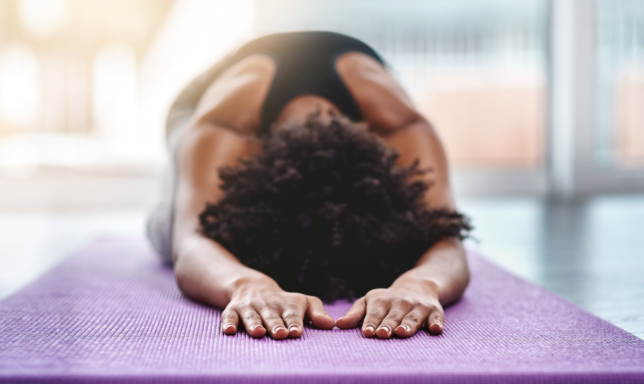 Shot of a beautiful young woman practising yoga in a studio