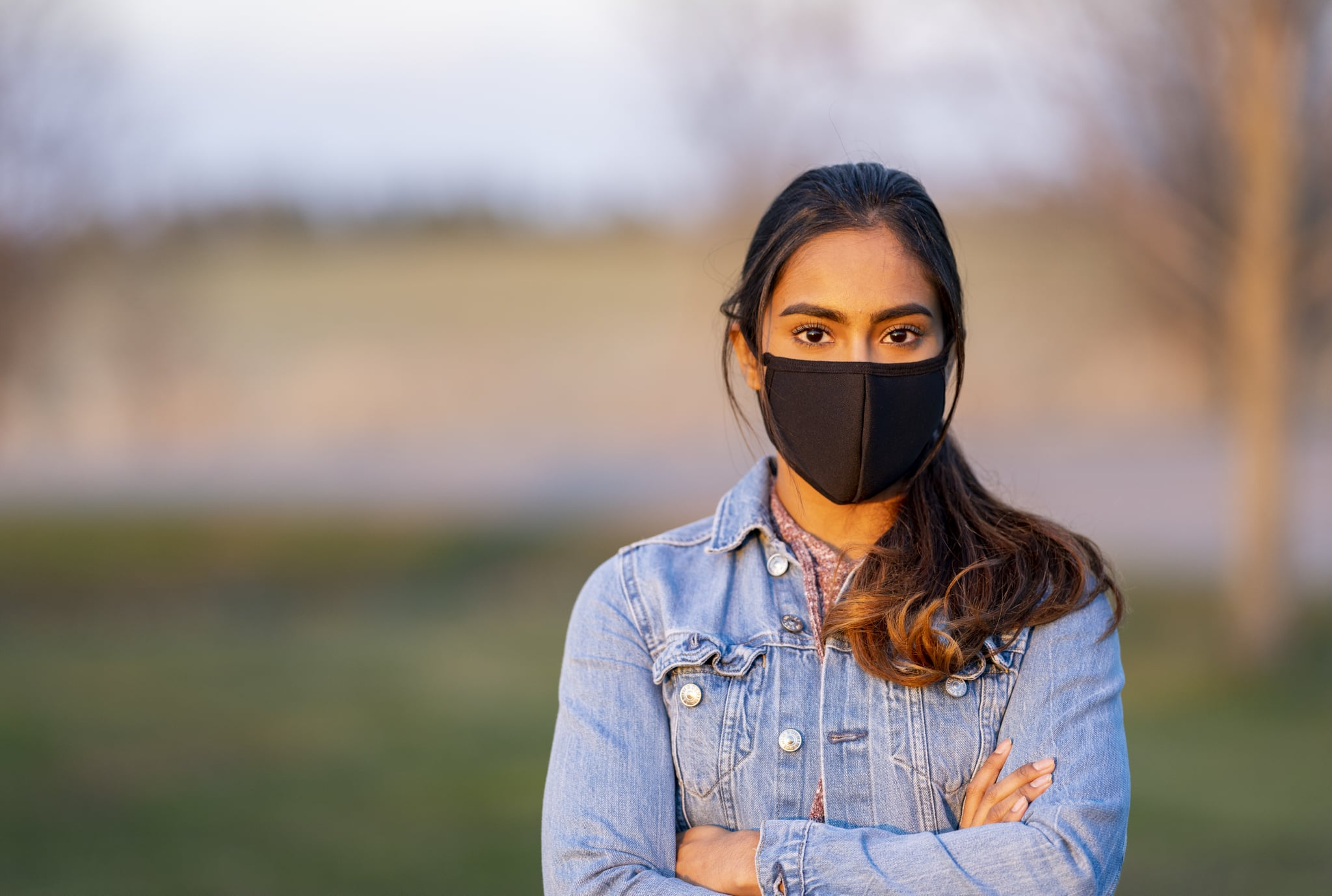 Ethnic girl standing outside wearing a protective mask during a beautiful sunset.