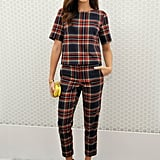 Ashley Madekwe joined Topshop to celebrate the holidays in a seasonal print. Her plaid a bold choice, but her bright accessories really made this outfit pop.