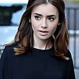 Lily Collins had a slight '60s vibe to her beauty look while in the UK. Light pink lipstick, a voluminous blowout, and a flick of eyeliner were the key elements of her look.