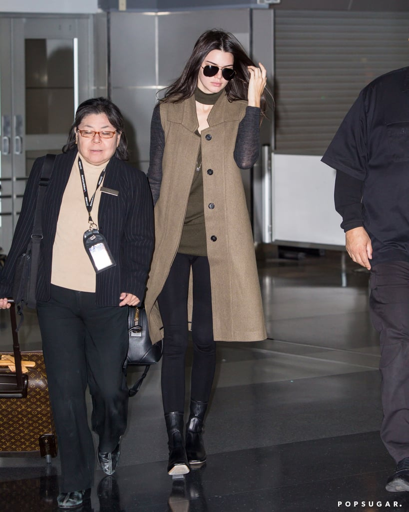Kendall rocked her black leather Givenchy bag at the airport with a longline vest, an olive top, skinny jeans, and boots.