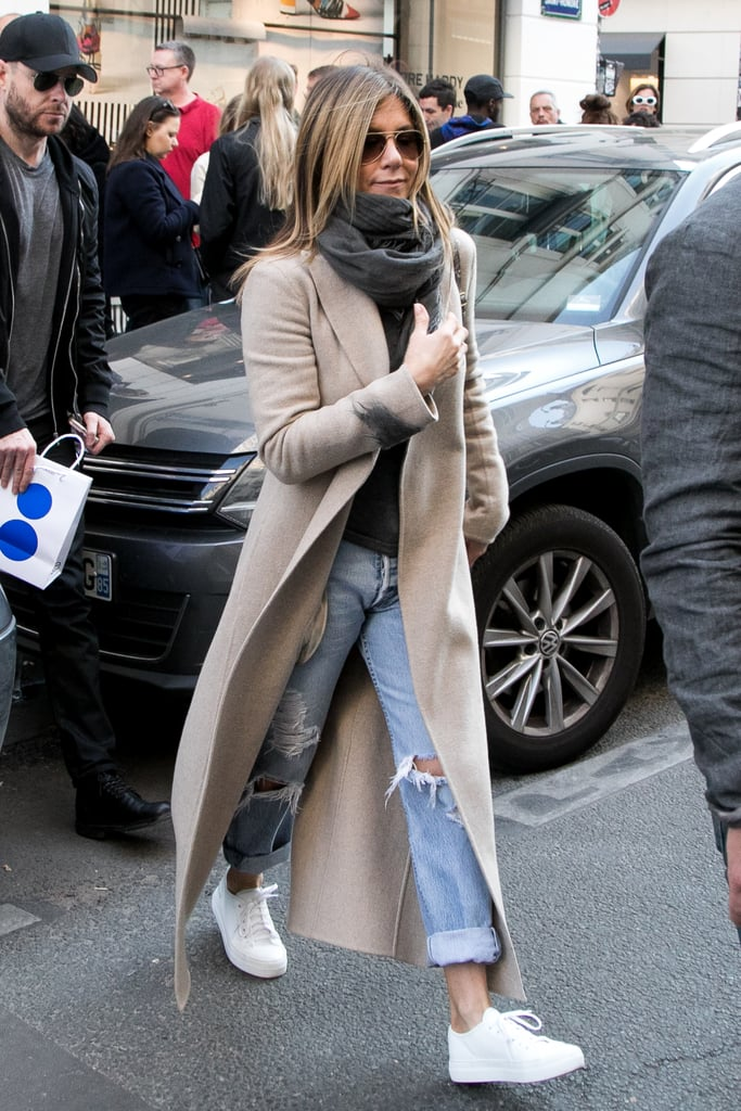 In April 2017, Jennifer wore ripped boyfriend jeans with simple white sneakers, a camel coat, lightweight scarf, textured crossbody bag, and aviator sunglasses.